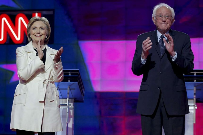 Democratic US presidential candidates Hillary Clinton (left) and Senator Bernie Sanders applaud together before the start of a debate hosted by CNN and New York One at the Brooklyn Navy Yard in New York Apr 14, 2016.
