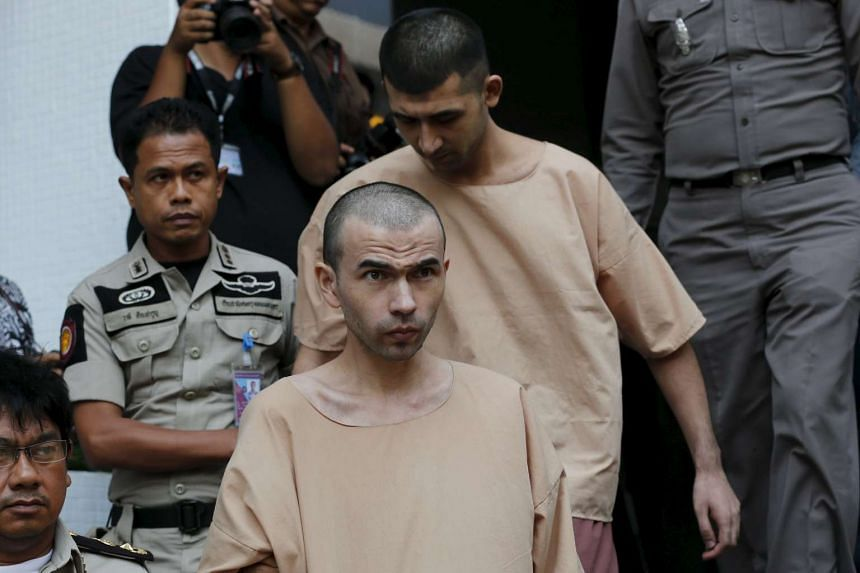 Bangkok blast suspects Adem Karadag (front) and Yusufu Mieraili are escorted by prison officers as they leave the military court in Bangkok, Thailand on April 21, 2016.