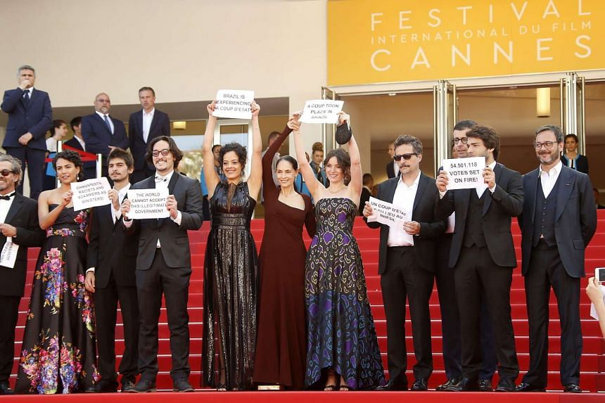 Brazilian actress Maeve Jinkings, Brazilian actress Sonia Braga, producer Emilie Lesclaux, Brazilian director Kleber Mendonca Filho and guests hold signs such as one reading 'A coup took place in Brazil' as they arrive for the screening of 'Aquarius'