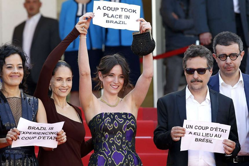 (From left) Brazilian actress Maeve Jinkings, Brazilian actress Sonia Braga, producer Emilie Lesclaux and Brazilian director Kleber Mendonca Filho hold signs reading 'A coup took place in Brazil', 'Brazil is experiencing a coup d'etat' as they arrive