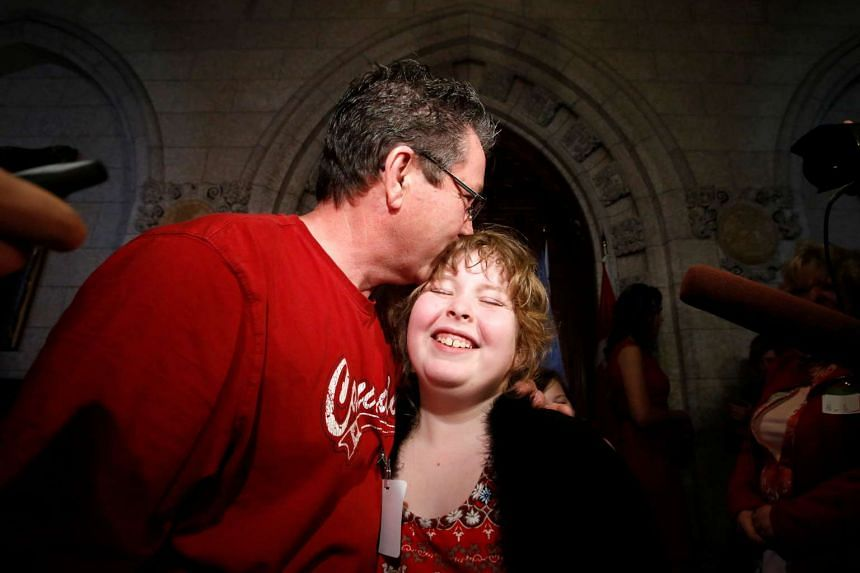 Charlie Lowthian-Rickert, 10, who is a transgender, is kissed by her father Chris following a news conference announcing that Canada will introduce legislation to protect transgender people from discrimination and hate crimes.
