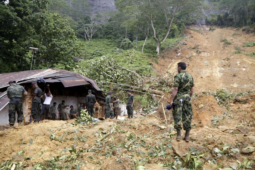 Sri Lanka Armed Forces personnel engage in rescue operations at the landslide area where 16 persons have been reported missing at Kalupahanawatte in Bulathkohupitiya, 97km towards the central hills from Colombo, Sri Lanka, on May 18, 2016. By morning