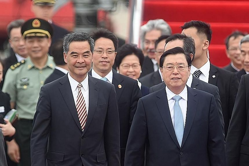 Mr Zhang (at right) accompanied by Mr Leung after arriving at Hong Kong's airport yesterday. Mr Zhang is the most senior Chinese official to visit Hong Kong since the 79-day Occupy movement in 2014 to push for unfettered elections.