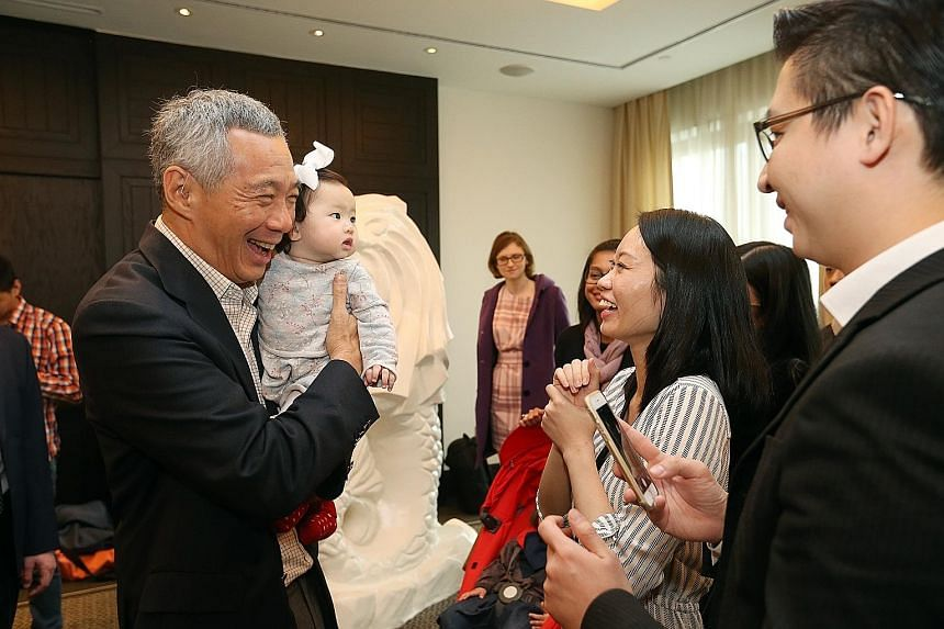 PM Lee meeting Singaporeans Derrick and Melissa Leow, both 32, at a reception in Moscow yesterday. He is holding their seven-month-old daughter, Charlotte. He will fly to Sochi tomorrow to attend the Asean-Russia Commemorative Summit, which marks 20