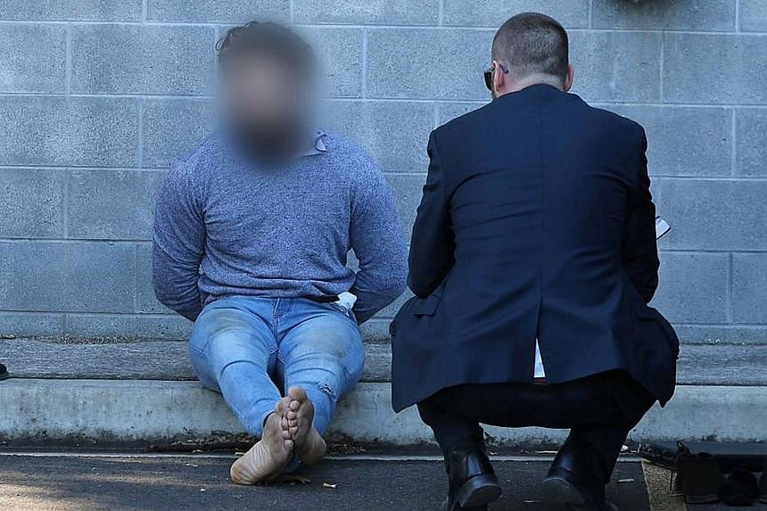 Tamim Khaja being arrested in Sydney yesterday. Australian police say he was trying to acquire a firearm and was also planning to leave the country to join the ISIS militant group.