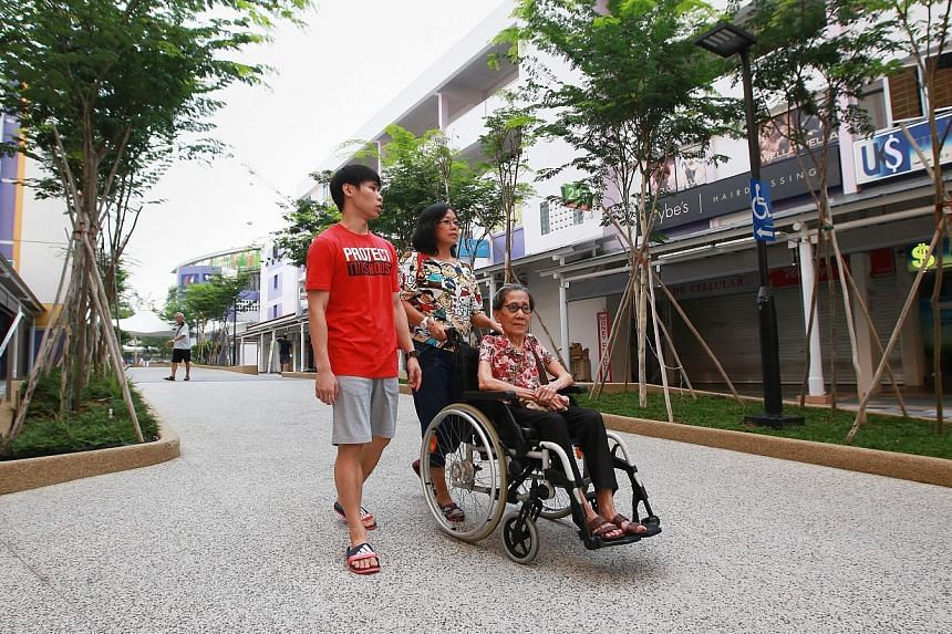 More ramps and signs installed after Bedok's upgrading works make it easier for wheelchair users like Madam Yeo, 77, seen here with her daughter Cheng See and grandson Kang Rui Jie, 21. The upgrades are part of the Housing Board's Remaking Our Heartl