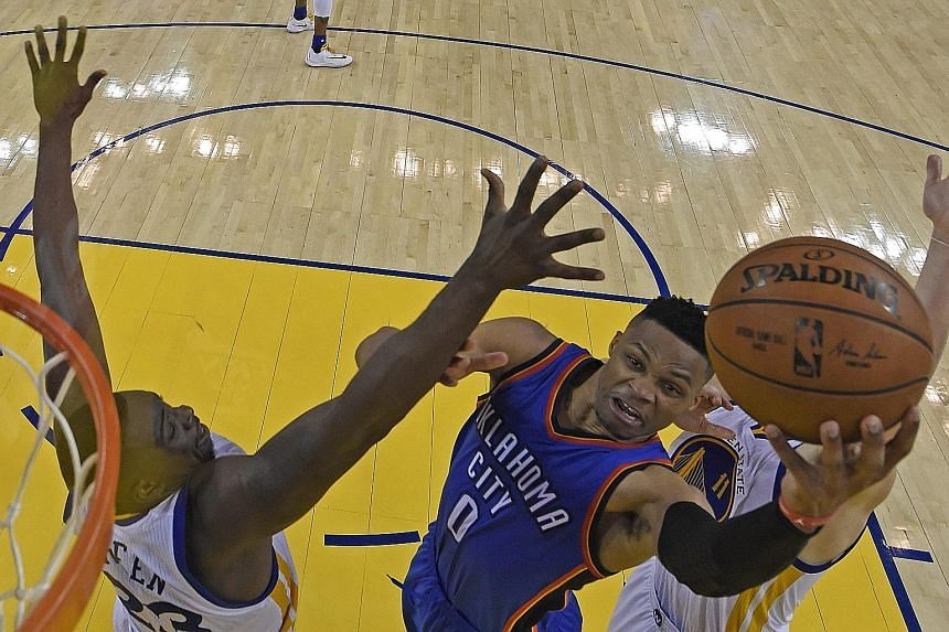 Thunder guard Russell Westbrook (centre) drives to the basket as Warriors forward Draymond Green attempts to defend.