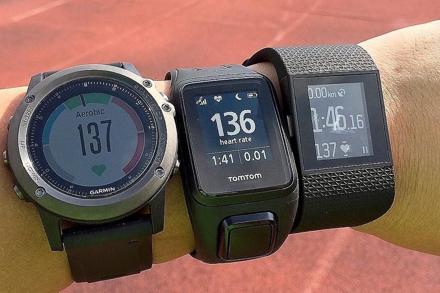 GPS running watches with built-in wrist-based heart rate monitors: (from left) the Garmin Fenix 3 HR, the TomTom Spark Cardio and the Fitbit Surge