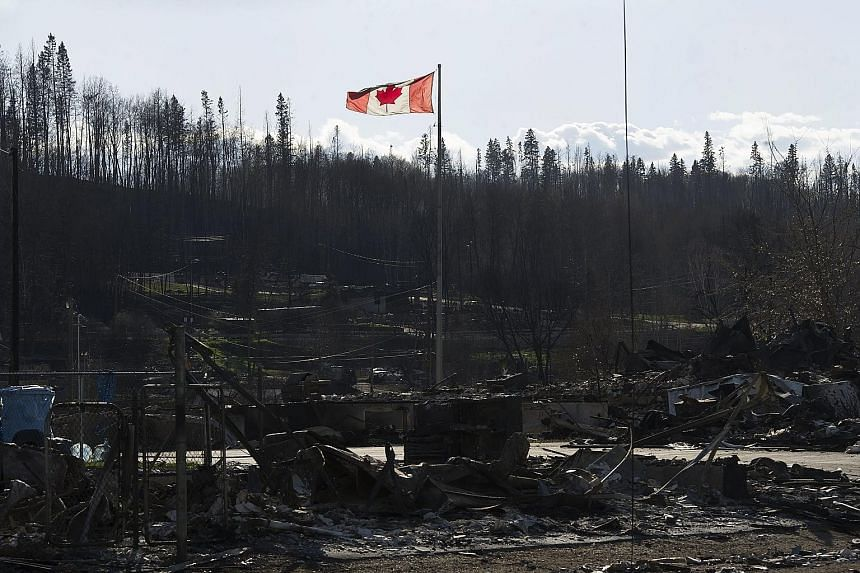 Damage caused by a wildfire that swept through some neighbourhoods in Fort McMurray, Alberta, last Saturday. The latest mandatory evacuation alert covered 12 work camps north of the city.