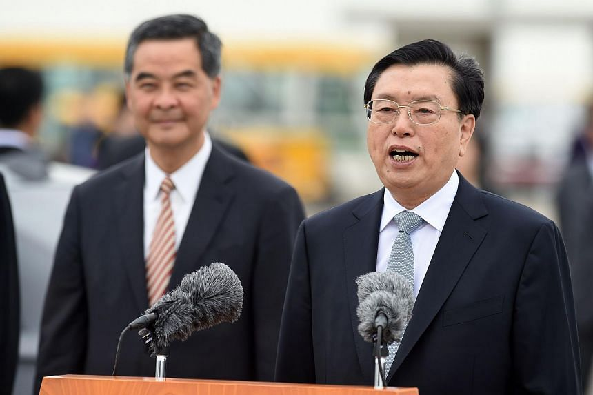 China's National People's Congress (NPC) Standing Committee Chairman Zhang Dejiang (right) speaking to the media next to Hong Kong's Chief Executive Leung Chun-ying (left) after arriving at Hong Kong's International Airport on May 17, 2016.
