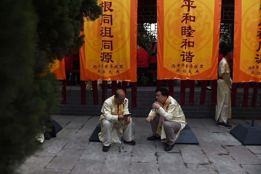 Two men chatting before a memorial ceremony for the Yellow Emperor in Xinzheng, in China's Henan province on April 9, 2016.