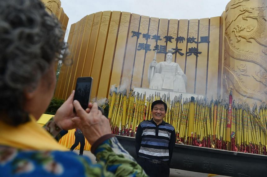 A man posing for photos in front of a statue of the Yellow Emperor after a memorial ceremony in Xinzheng, in China's Henan province on April 9, 2016.