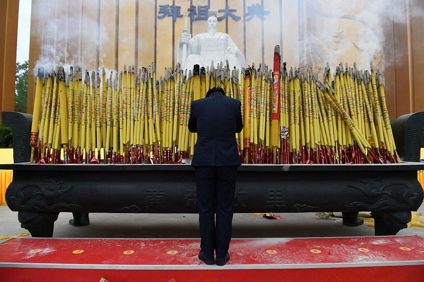 A man paying his respects in front of a statue of the Yellow Emperor, or Huangdi, after a memorial ceremony in Xinzhen, Henan, on April 9, 2016.
