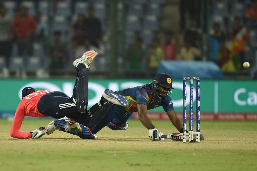 Sri Lanka's Angelo Mathews (right) completes a run as England wicketkeeper Jos Buttler dives during their World T20 cricket tournament match.