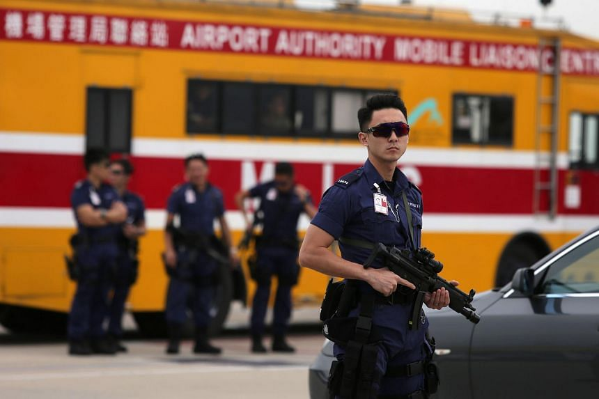 Armed Hong Kong police stand guard before the arrival of China's National People's Congress (NPC) Standing Committee Chairman Zhang Dejiang at Hong Kong's International Airport.