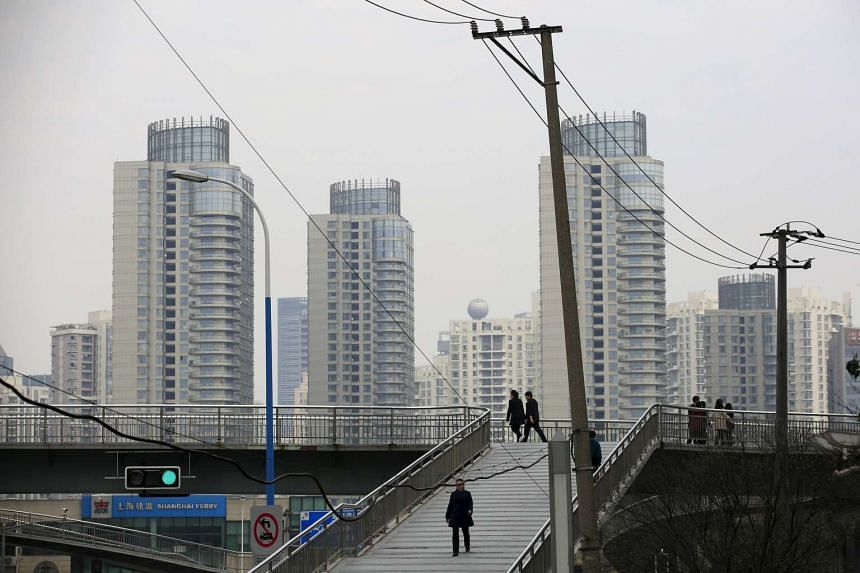 People walk on a bridge near the financial district of Pudong in Shanghai.
