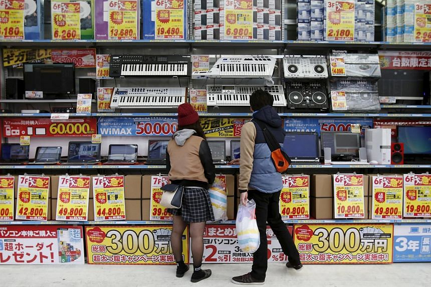 People trying out laptops displayed at an electronics retail store in Tokyo in this Nov, 16, 2014, file photo.