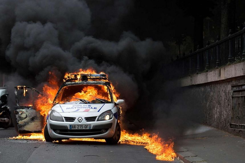 A police car burns after being set on fire during an unauthorised counter-demonstration against police violence on May 18, 2016 in Paris.