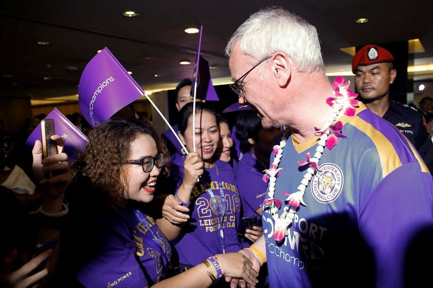 Claudio Ranieri shakes hands with supporters as he arrives with his team at Bangkok's Suvarnabhumi International Airport.