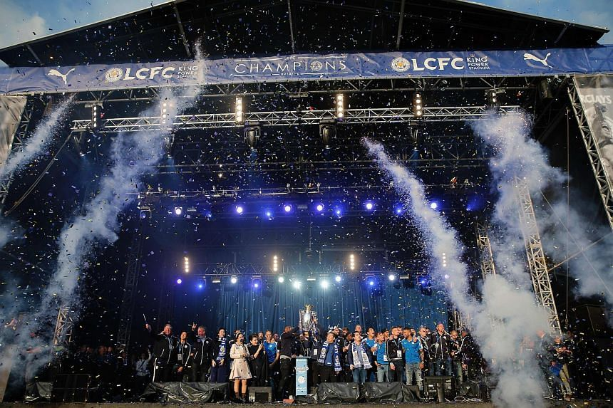 Leicester City's English captain and defender Wes Morgan and Leicester City's Thai owner and chairman Vichai Srivaddhanaprabha holding up the Premier league trophy to fans as the Leicester City team celebrate in Victoria Park on May 16, 2016.