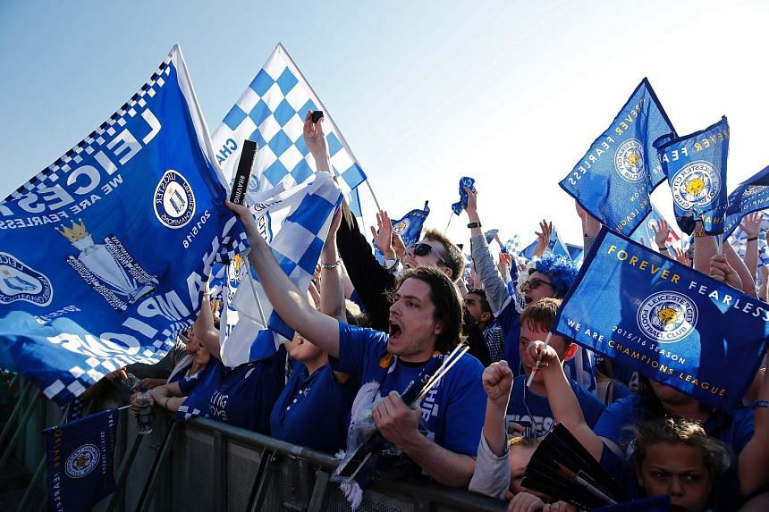 Leicester City football fans waving banners as they wait to see the Leicester City players pose with the Premier League trophy as the team arrive to celebrate in Victoria Park, on May 16, 2016.