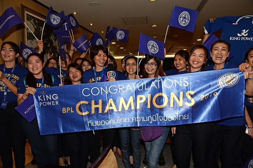 Leicester City fans cheer as Leicester City players arrive at Bangkok's Suvarnabhumi Airport.