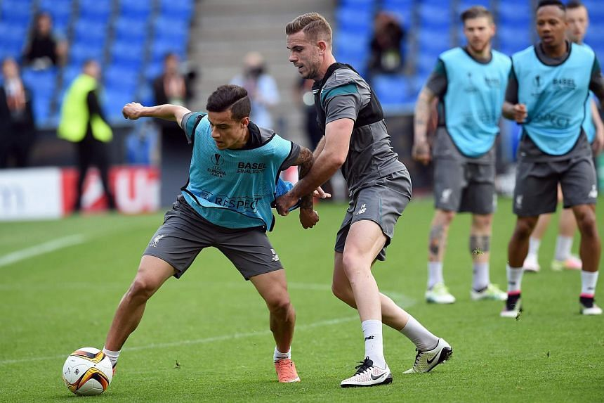 Liverpool's Brazilian midfielder Philippe Coutinho (left) and Liverpool's English midfielder Jordan Henderson vie for the ball as they attend a training session at the St Jakob-Park stadium in Basel, northern Switzerland, on May 17, 2016.