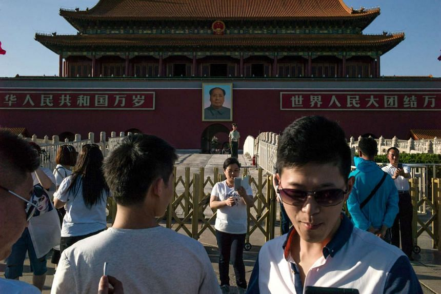 Tourists pose in front of a giant portrait of Mao Zedong at the gate of the Forbidden City in Beijing on May 16, 2016.  Official Chinese media stayed largely silent about Monday's 50th anniversary of the start of the bloody Cultural Revolution, with