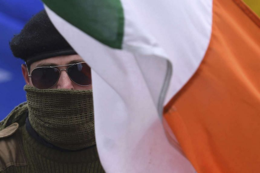 A masked member of Republican Sinn Fein during a commemorative event in Northern Ireland on March 26, 2016.