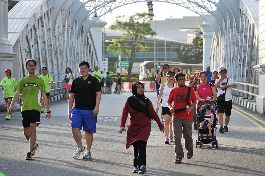 Families and joggers walking down the streets of the Civic District and Central Business District at the first Car-Free Sunday SG event on Feb 28, 2016.