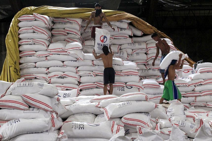 Workers carrying sacks of rice inside a National Food Authority (NFA) warehouse in Taguig city, south of Manila, on Aug 25, 2015.