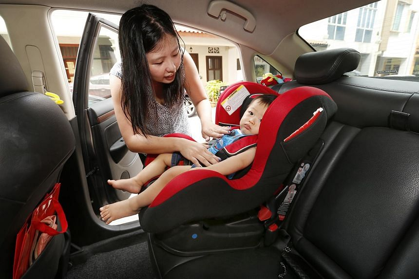 Ms Madeline Heng putting her son Joash, one, in a child seat.