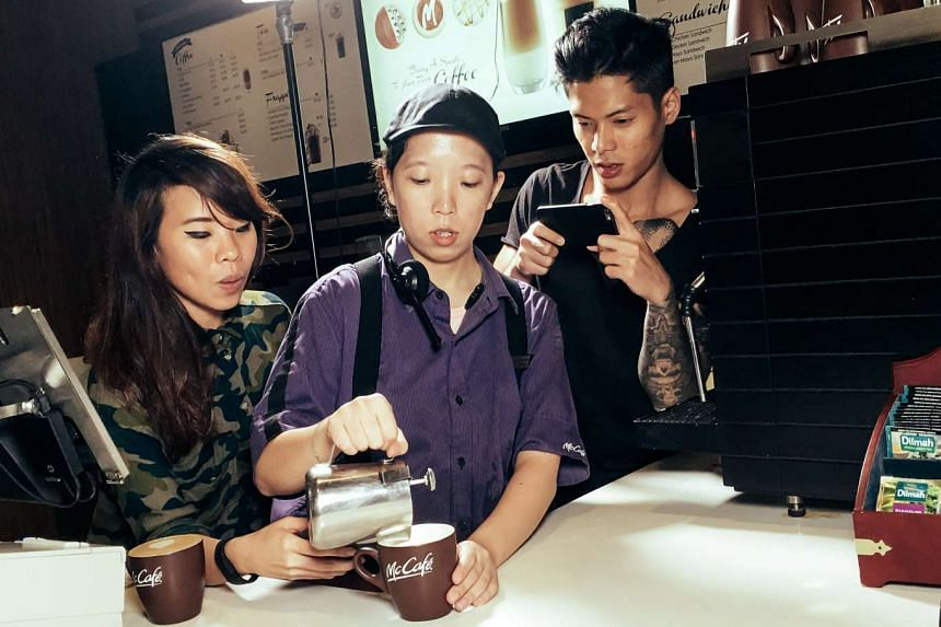 Riot !n Magenta's Eugenia Yip (above left) and band member Ritz Ang looking on as a McCafe employee makes a cup of joe.