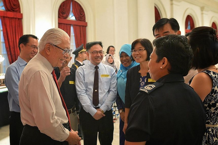 President Tony Tan Keng Yam speaking to civil servants, including Immigration and Checkpoints Authority Checkpoint Inspector (2) Zarina Zainee at an Istana reception yesterday evening. Some 500 public officers attended this year's reception, hosted b