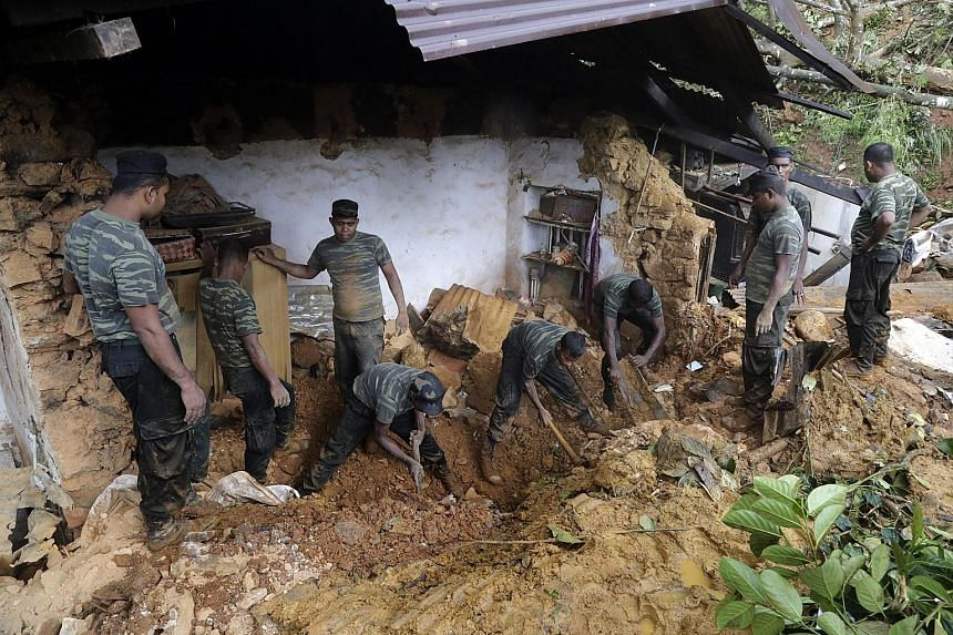 Sri Lankan military personnel looking for villagers buried in landslides yesterday.