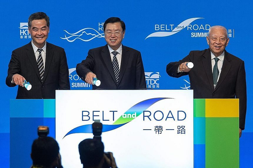 Mr Zhang Dejiang (centre), with Mr Leung Chun Ying (left) and former Hong Kong chief executive Tung Chee Hwa, at the opening ceremony of the Belt and Road Summit in Hong Kong yesterday. Protesters in Hong Kong yesterday demonstrating against the visi