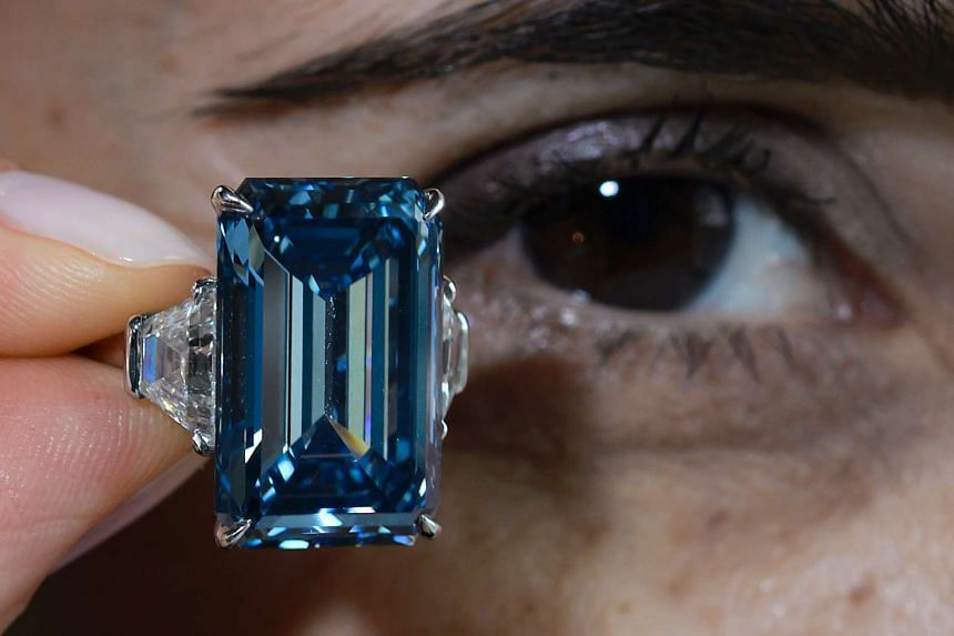 """A woman holds up the """"Oppenheimer Blue""""."""
