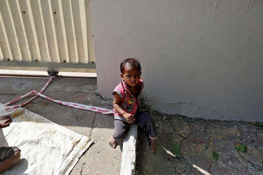 Barrier tape is tied around 15-month-old Shivani's ankle to prevent her from running away.