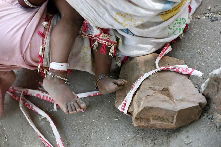 Construction worker Sarta Kalara feeds her daughter Shivani as one end of a barrier tape is tied to Shivani's foot and the other to a stone.