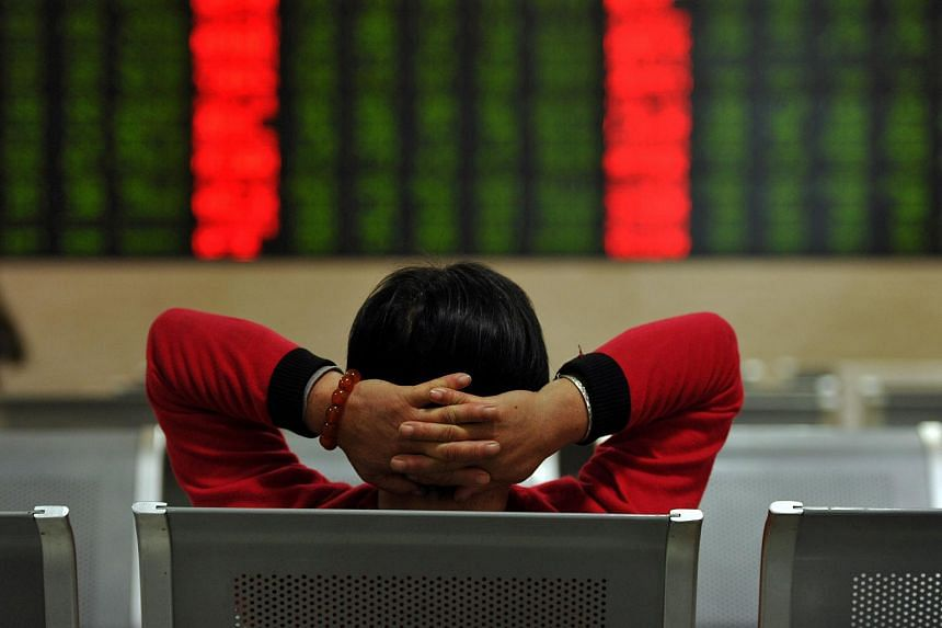 An investor sits in front of a screen showing stock market movements at a securities firm in Fuyang.