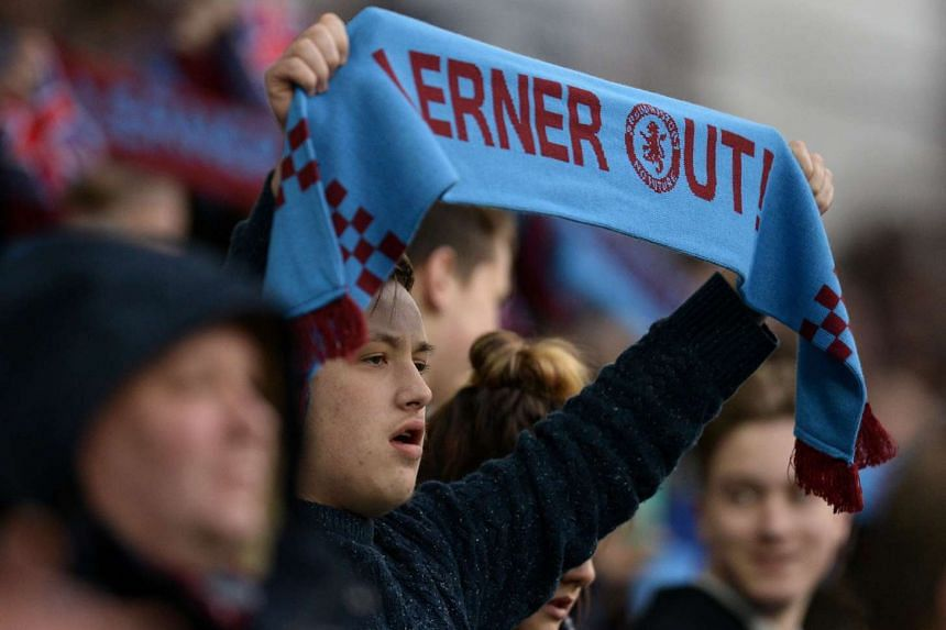 """A fan holds a scarf reading """"Lerner Out"""" in reference to Aston Villa's US chairman Randy Lerner  in March 2016."""