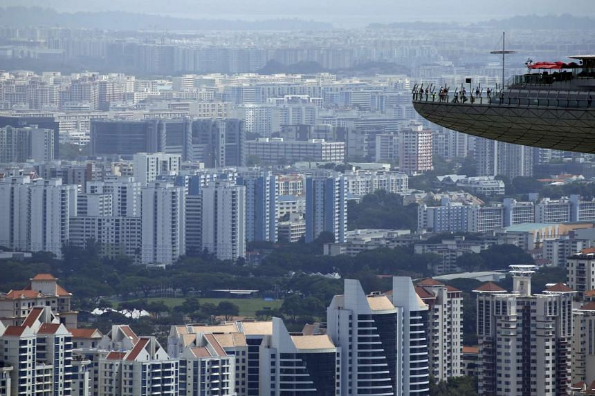People look out from the observation tower of the Marina Bay Sands amongst public and private residential apartment buildings in Singapore.
