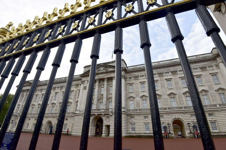 Buckingham Palace is seen through the perimeter fence in central London, Britain, on Oct 24, 2014.