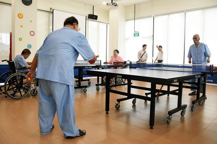 Volunteers in Yuhua estate join residents of the new All Saints Home in Jurong East to play table tennis.