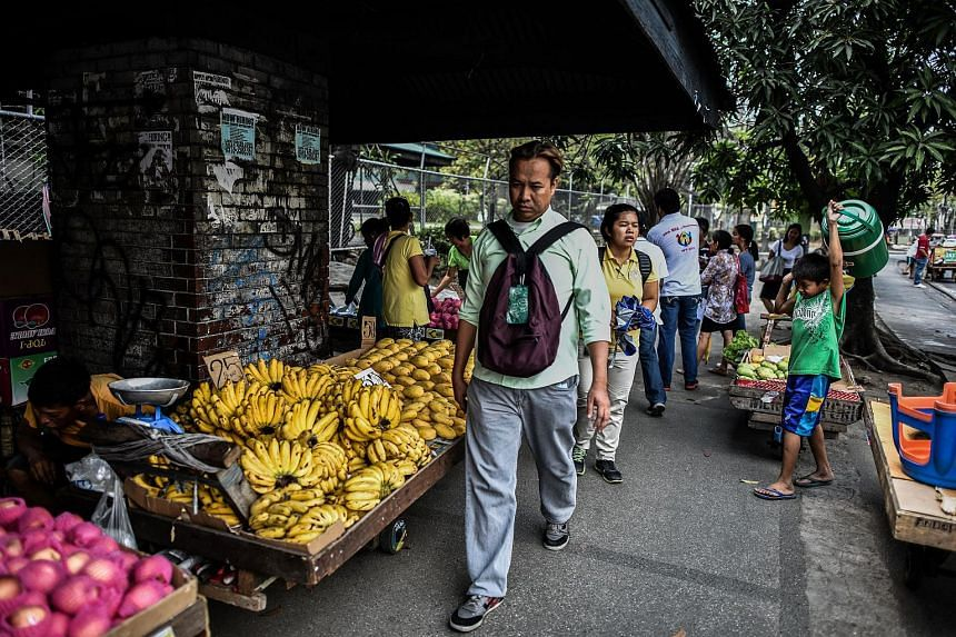 Filipinos walk past roadside stalls in Manila on May 10, 2016, a day after the country went to the polls in the presidential election.