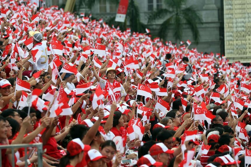 Spectators waving the mini Singapore flags during the Golden Jubilee National Day Parade (NDP) at the Padang on Aug 9, 2015.