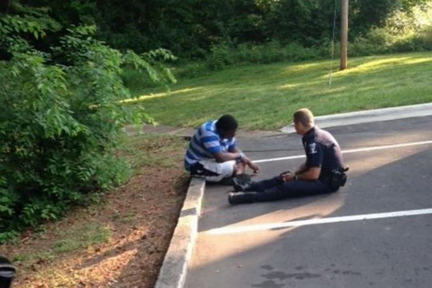 Police officer Tim Purdy chatting with the teenager, who had wandered away from his high school campus.