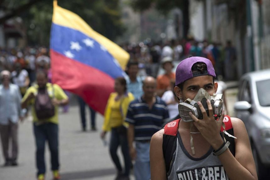 A protester wears a respirator mask during a demonstration in support of a referendum on the rule of President Nicolas Maduro in Caracas, Venezuela, May 18, 2016.
