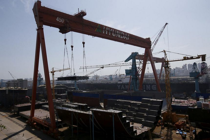 A part of the structure of a ship (bottom centre) is lifted by giant crane at Hyundai Heavy Industries' Shipyard in Ulsan, South Korea.
