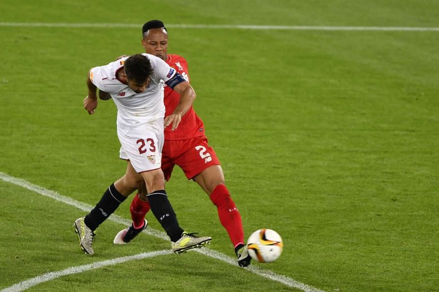 Sevilla's captain Coke (left) shoots and scores his team's second goal past Liverpool's defender Nathaniel Clyne.